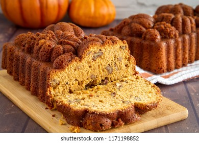 Sliced loaf of pecan pumpkin bread sitting on wooden cutting board with full loaf in background on orange striped towel