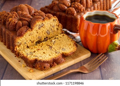 Sliced loaf of pumpkin bread sitting on wooden cutting board with full loaf in background and cup of coffee in pumpkin mug