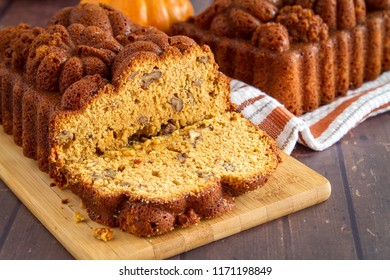 Sliced loaf of pumpkin bread sitting on wooden cutting board with full loaf in background on orange striped towel with space for text