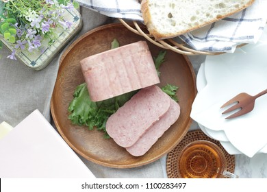 Sliced luncheon meat on wooden plate