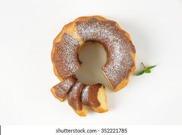 sliced marble bundt cake on white background