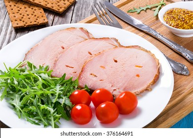 sliced meat with arugula salad, cherry tomatoes on the white dish with french mustard sauce in gravy boat on a cutting board, top view, closeup