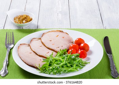 Sliced meat with arugula salad, cherry tomatoes on a white dish , top view, closeup