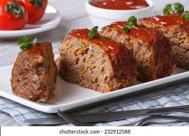 Sliced meat loaf with ketchup and parsley close-up on a plate, horizontal