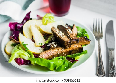 Sliced meat steak with green salad and pears