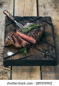 Sliced medium rare grilled beef steak with salt, pepper and rosemary on meat cutting board on dark wooden background