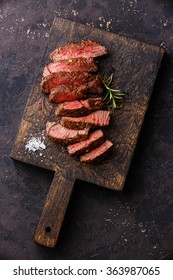 Sliced medium rare grilled Beef steak on wooden cutting board