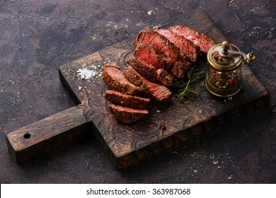 Sliced medium rare grilled Beef steak and pepper mill on wooden cutting board