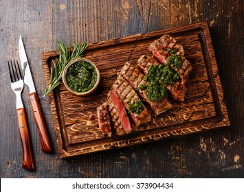 Sliced medium rare grilled beef barbecue Sirloin steak with chimichurri sauce on cutting board on dark background