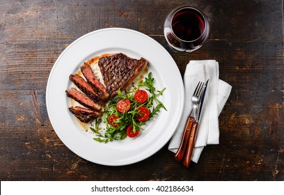 Sliced medium rare grilled Beef steak Striploin, salad with tomatoes and arugula on white plate and red wine on dark wooden background