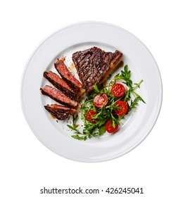 Sliced medium rare grilled Beef steak Striploin and salad with tomatoes and arugula on white plate isolated
