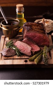 Sliced medium rare grilled Beef steak with rosemary and garlic  on wooden board