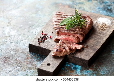 Sliced medium rare grilled beef steak on wooden cutting board, selective focus