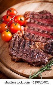 Sliced medium rare grilled Beef steak Ribeye with cherry tomatoes on cutting board, , selective focus