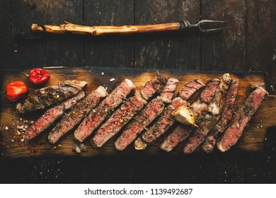 Sliced medium rare grilled steak ribeye with salt, spices, and rosemary