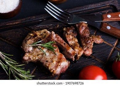 Sliced medium rare grilled steak with spices on wooden  board.