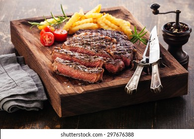 Sliced medium rare grilled Steak Ribeye Black Angus with french fries on serving board block on wooden background
