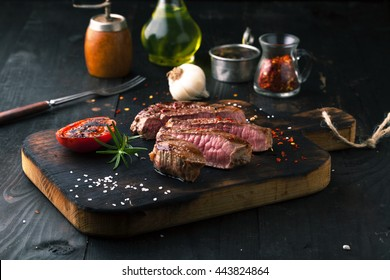Sliced medium rare grilled Steak Ribeye with rosemary on a dark background