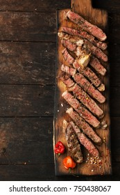 Sliced medium rare grilled  steak ribeye with salt, spices, and rosemary on  wooden cutting board