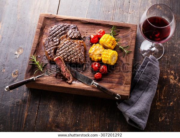 Sliced Medium rare grilled Steak Ribeye Black Angus with corn and cherry tomatoes on serving board block on wooden background