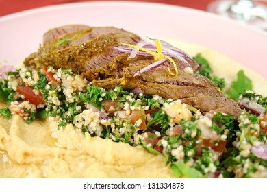 Sliced Middle Eastern lamb fillet with hommus and tabouleh.