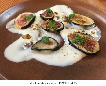 Sliced mission figs topped with mint in white yogurt topped with pistachios