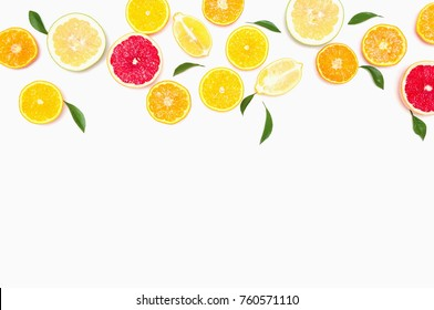 Sliced mixed citrus fruits as a background, healthy eating concept, diet.Citrus fruit slices with green leaves on a white background,banner for website. Flat lay, top view, copy space