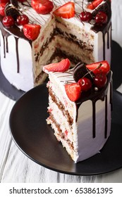 sliced mousse cake with fresh strawberry and cherry, decorated with chocolate closeup. vertical