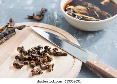 Sliced mushrooms on wooden board. Soaking mushrooms.