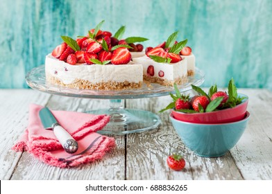 Sliced No Bake Strawberry Cheesecake Decorated with Fresh Berries and Mint