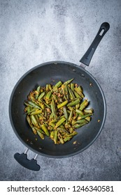 Sliced okra pieces in a wok, fried in Indian spices ready to be served as a side dish. The curry is on a dark grey background is used.