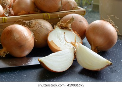 a sliced onions with a basket of onions and knife