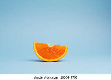 sliced orange fruit isolated on blue background, minimalistic pop art color concept