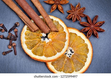 Sliced of orange fruits with cinnamon sticks, star anise and cloves on slate