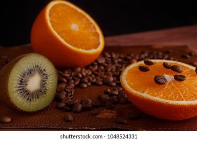 sliced orange and kiwi with coffee beans on burlap background and wood table