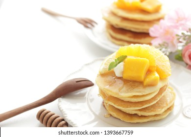 Sliced orange and Mango on homemade pancake for breakfast image