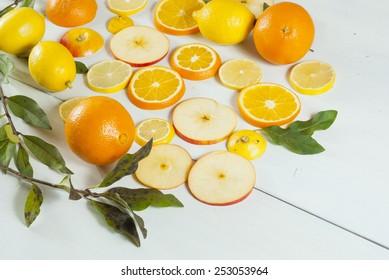 sliced oranges, apples and lemons on white wood
