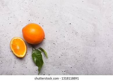 Sliced oranges on a gray background, top view. This fruit is a source of vitamins and raw materials for making juice