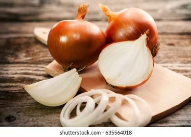 A sliced organic onion and fresh onions on cutting board