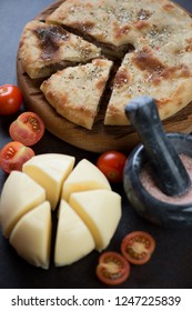 Sliced ossetian pie with meat, suluguni cheese and tomatoes, selective focus, close-up