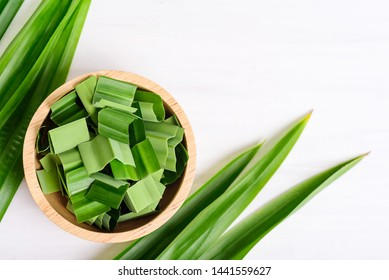 Sliced pandan leaf in a bowl and fresh pandan leaf on white background, pandan leaf used to enhance the flavoring and color in Asia food and dessert