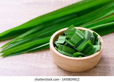 Sliced pandan leaf in a bowl on wooden background, pandan leaf used to enhance the flavoring and color in Asia food and dessert