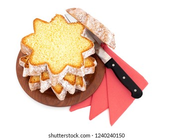 Sliced pandoro, Italian sweet yeast bread, traditional Christmas treat. With red serviettes and knife on white. Overhead flat lay view.