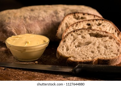 Sliced Panini bread with butter in a bowl on a wooden board photographed in a darkfood style