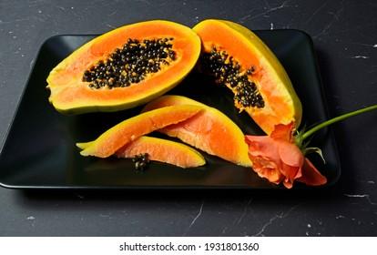 sliced papaya fruit with black seeds