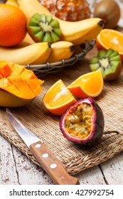 sliced passion fruit and tropical fruits in assortment: bananas, kiwi, mango, pineapple, orange