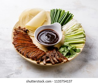 Sliced Peking Duck served with Hoysin sauce, fresh cucumber, onions, cilantro and roasted wheaten pancakes on white wooden background