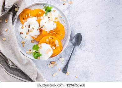 Sliced persimmon with yogurt and almonds. Healthy food concept on light background. top view