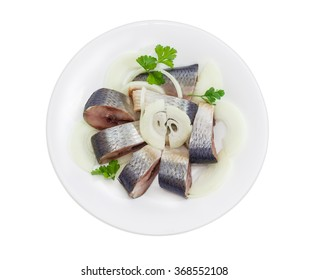 Sliced pickled atlantic herring, chopped onions and parsley leaves on a white dish on a light background