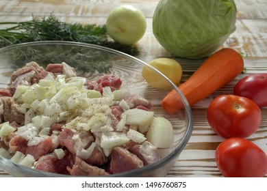 Sliced pieces of fresh meat and onions in a glass baking dish, sprinkled with black pepper and lying next to the whole clean vegetables. The process of cooking the Orlov-style meat. Closeup.